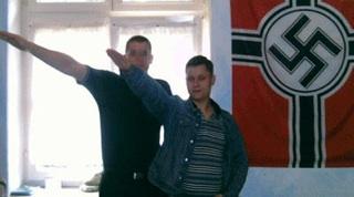 NPD-Bundestagskandidat Philipp Hasselbach (re.) mit zum Hitlergruß ausgestreckten Arm vor einer NS-Reichskriegsflagge mit Hakenkreuz