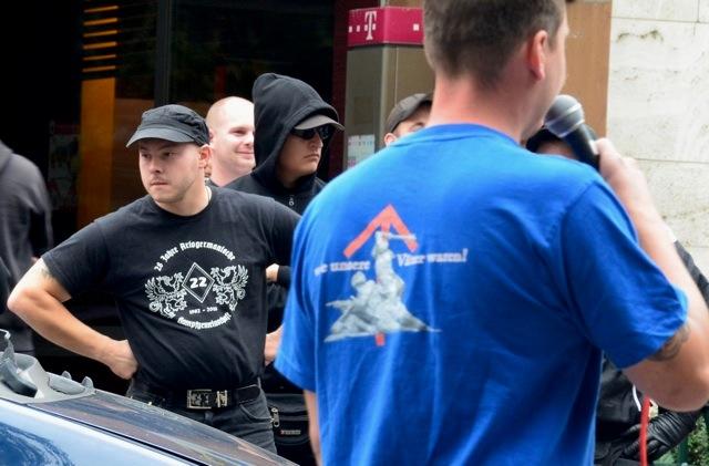 links: Karl Heinz Statzberger mit 'Vandalen'-T-Shirt. Rechts: Verbotene Tyr-Rune auf dem T-Shirt des Redners Philippe Eglin.  Foto: recherche-bayern