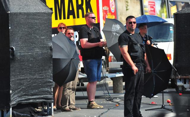 Kundgebungsredner Ralf Ollert versteckt sich hinter Regenschirmen. Foto: Timo Müller
